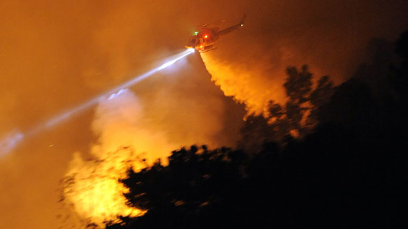 A Los Angeles County fire helicopter does a drop over a hotspot in Rancho Palos Verdes on Aug. 28, 2009. (Mark J. Terrill/Associated Press)