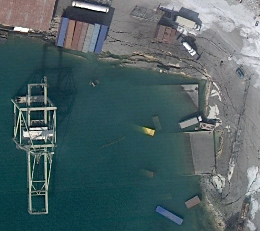 The harbor in Haiti. You can see one of the cranes used for unloading cargo has fallen into the ocean. Cracks in the pavement or ground can bee seen in the upper right.