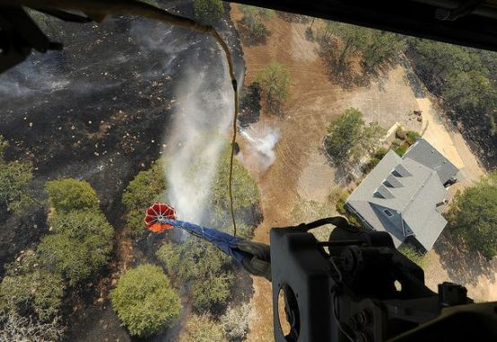 Looking down from a Ch-47 as it drops water on a fire