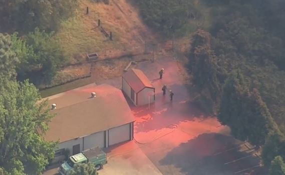 Firefighters near a house on the Summit fire a few seconds after a retardant drop by a P2V air tanker. (screen grab from ABC7 video)