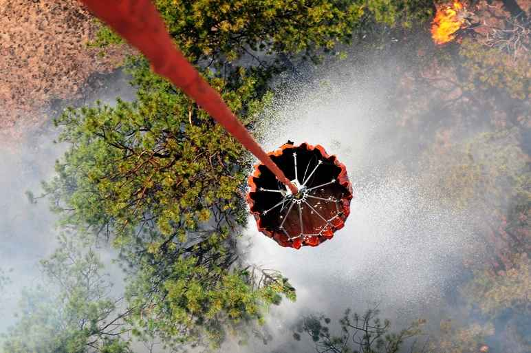 U.S. Army pilots and crew members with the 2nd General Support Aviation Battalion, 4th Aviation Regiment, 4th Combat Aviation Brigade, 4th Infantry Division, release water with a helicopter bucket over the Black Forest Fire