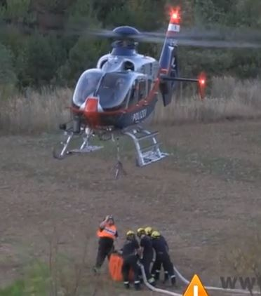 Firefighters refill a helicopter bucket