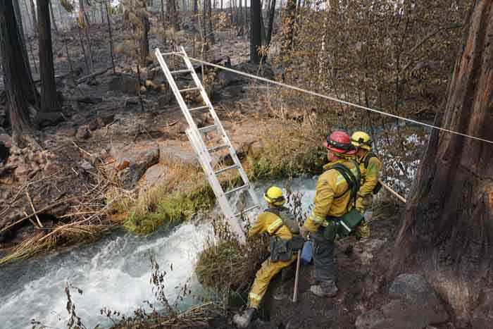 Tahoe Douglas engine crew installing a ladder across a creek adjacent to a house in order to mop up on the other side. Photo by Bill Gabbert.