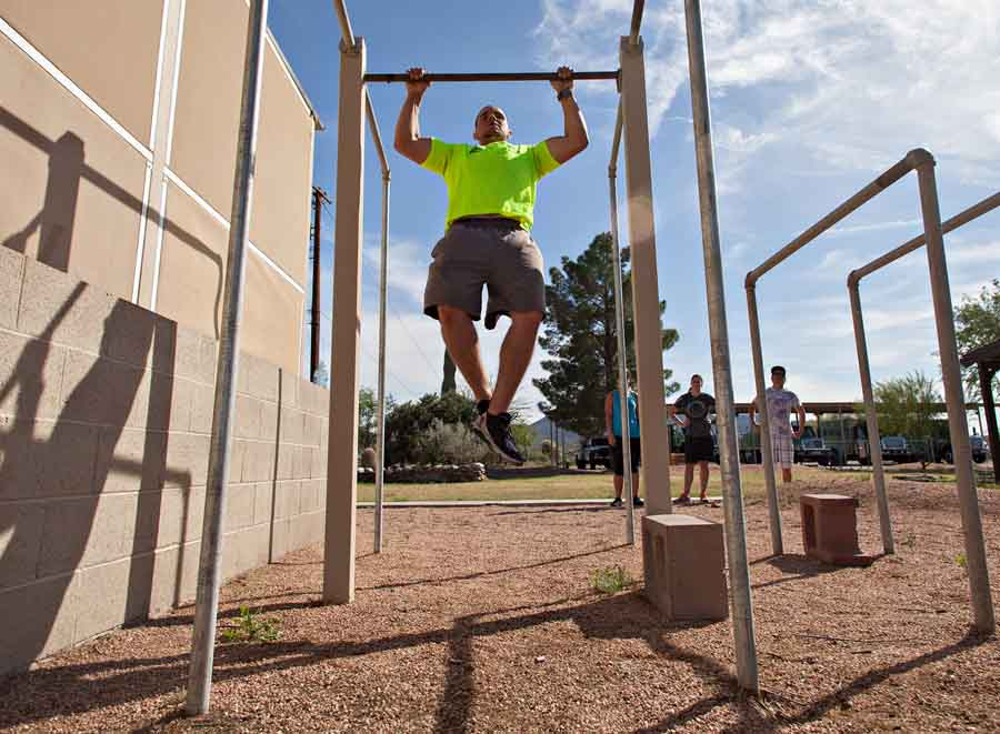 Corey Hall does pull ups as other members of the Mesa Hotshot watch and wait during the crews physical training test.