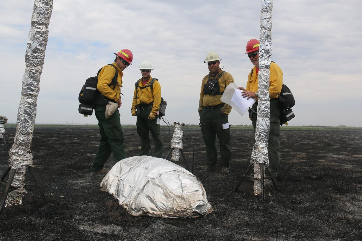 Left to right: Bobby Williams, Nick Mink/BLM, Blake Stewart/USFWS, and Joe Roise inspect the fire shelter model currently used by firefighters, which was included in the field test for comparative purposes. Photo courtesy Great Plains Fire Management Zone