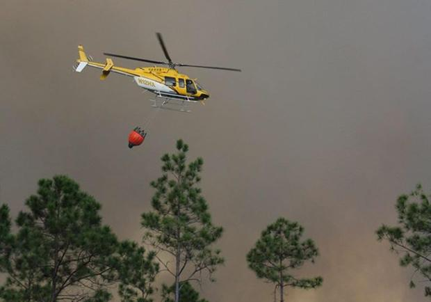 A helicopter carries a bucket of water on a drop at the fire in the Okefenokee National Wildlife Refuge. Photo via Inciweb, posted May 14, 2017.